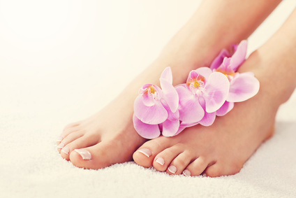 Female feet with french pedicure and flowers close up